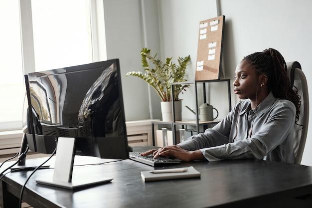 Vue latérale portrait d'une femme afro-américaine réussie utilisant un ordinateur tout en étant assise au bureau au bureau, concept de pdg féminin, espace de copie