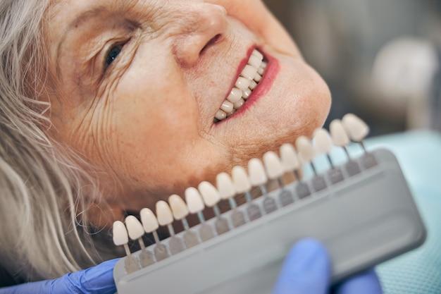 Vue latérale portrait d'une femme âgée souriante assise dans le cabinet dentaire tandis que le médecin en gant bleu tenant un membre artificiel en porcelaine