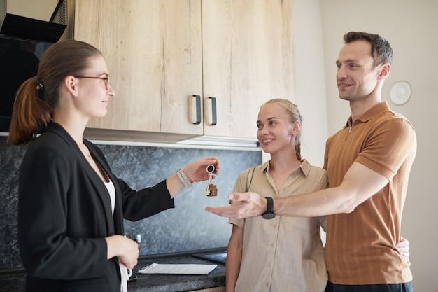 Vue latérale portrait d'une femme agent immobilier donnant les clés à un jeune couple achetant un appartement