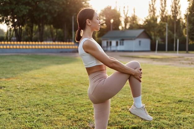 Vue latérale portrait d'une femme brune vêtue d'un haut blanc et de leggins beiges s'échauffant avant de s'entraîner dans le stade, étirant la jambe, regardant au loin.