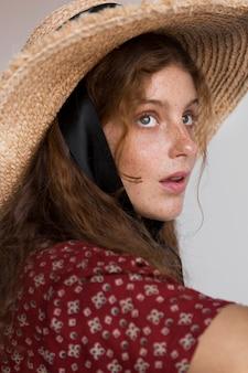 Vue latérale portrait de femme avec chapeau de paille