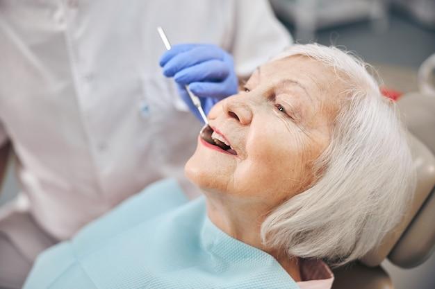 Vue latérale portrait d'une femme ouvrant la bouche lors d'un examen oral chez le dentiste de la clinique médicale