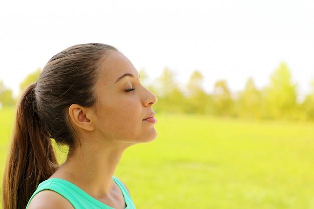 Vue latérale portrait de femme relaxante respirant l'air frais profondément dans le parc. copiez l'espace.