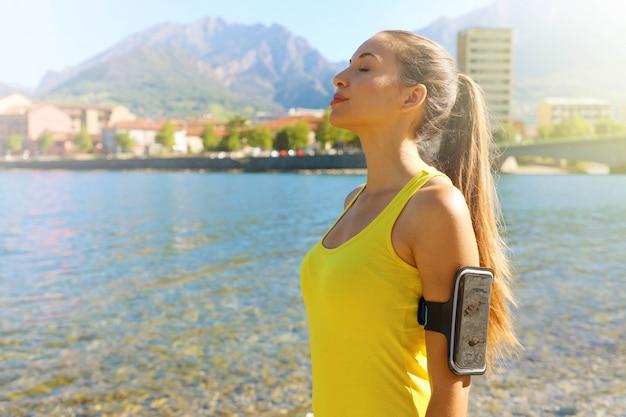 Vue latérale portrait d'une femme de remise en forme avec brassard pour téléphone intelligent se détendre en respirant l'air frais sur le lac de la ville le matin. copiez l'espace.