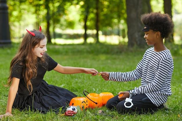 Vue latérale portrait de garçon et fille portant des costumes d'halloween et partageant des bonbons assis sur l'herbe verte à l'extérieur