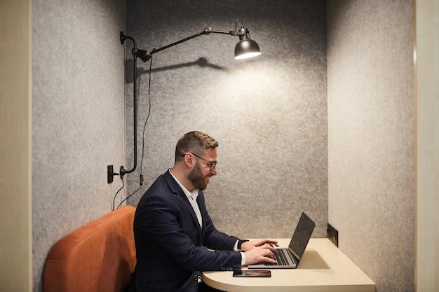 Vue latérale portrait d'homme d'affaires barbu souriant à l'aide d'un ordinateur portable tout en appréciant le travail dans la cabine de café au bureau, copiez l'espace