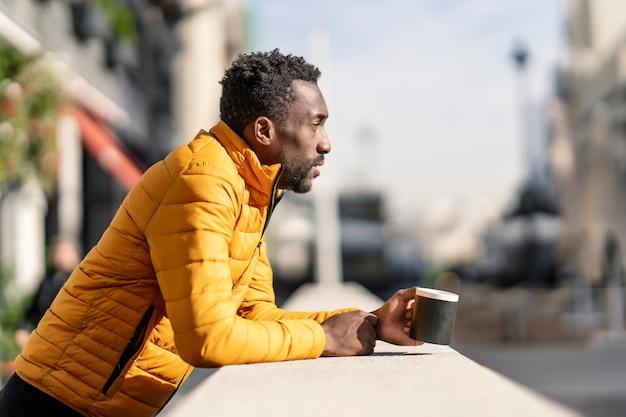 Vue latérale portrait d'un homme africain sérieux appuyé sur un balcon tenant une tasse de café en contemplant des vues dans une ville