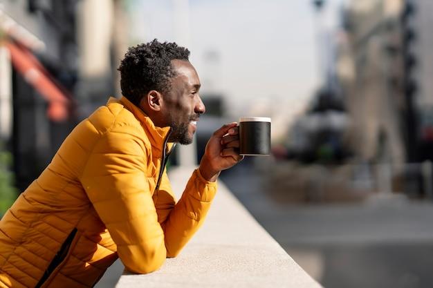 Vue latérale portrait d'un homme africain souriant appuyé sur un balcon tenant une tasse de café en contemplant des vues dans une ville