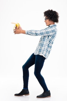 Vue latérale portrait d'un homme afro-américain drôle visant de la banane isolé sur un mur blanc