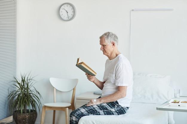 Vue latérale portrait d'un homme âgé lisant un livre à l'hôpital alors qu'il était assis sur son lit dans l'espace de copie de la salle blanche