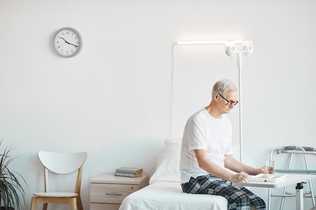 Vue latérale portrait d'un homme âgé mangeant de la nourriture à l'hôpital alors qu'il était assis sur son lit dans une salle blanche, espace pour copie