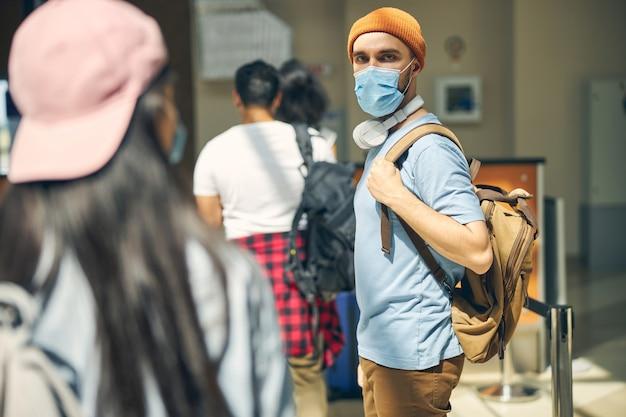 Vue latérale portrait d'un homme barbu portant un masque de protection avec sac à dos sur l'épaule posant devant l'appareil photo