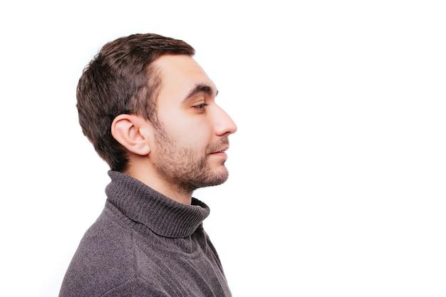Vue latérale portrait d'un homme caucasien magnifique avec des poils et des mains croisées regardant l'espace de copie, debout sur un mur blanc