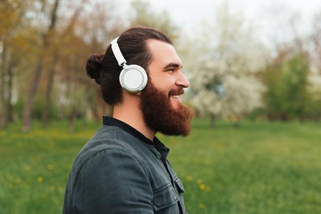 Vue latérale portrait d'un homme hipster barbu dans un parc en écoutant de la musique
