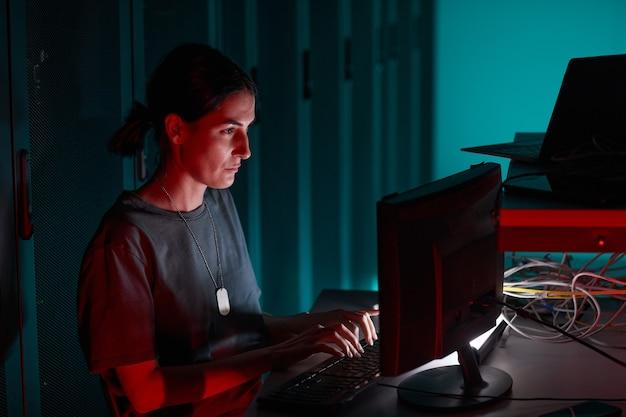Vue latérale portrait d'une ingénieure informatique utilisant un ordinateur tout en travaillant dans la salle des serveurs éclairée par la lumière rouge, espace de copie