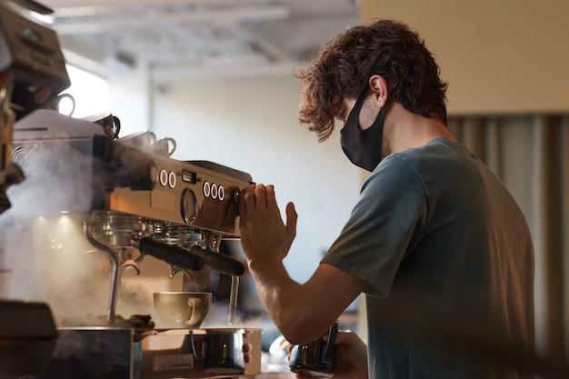 Vue latérale portrait d'un jeune barista portant un masque tout en préparant du café frais dans un café ou un café, espace pour copie
