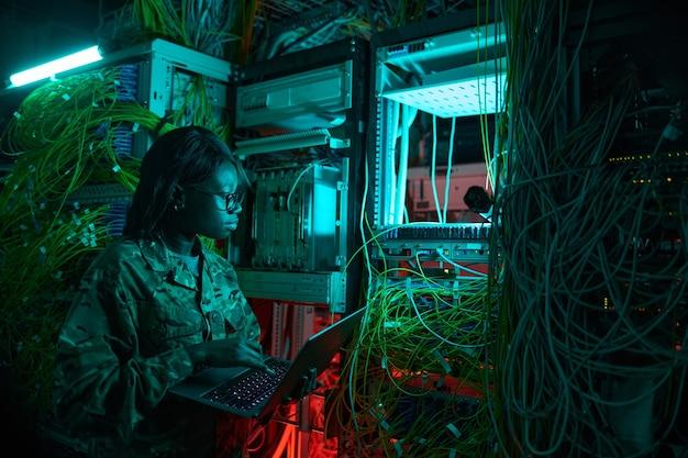 Vue latérale portrait d'une jeune femme afro-américaine portant un uniforme militaire inspectant le serveur tout en travaillant dans la salle des serveurs
