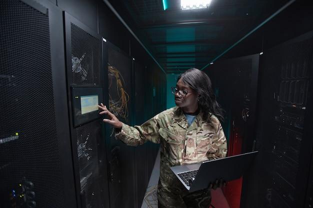 Vue latérale portrait d'une jeune femme afro-américaine portant un uniforme militaire utilisant un ordinateur portable tout en se tenant dans la salle des serveurs, espace pour copie