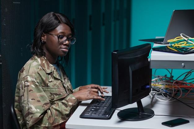 Vue latérale portrait d'une jeune femme afro-américaine portant un uniforme militaire utilisant un ordinateur tout en travaillant dans la salle des serveurs
