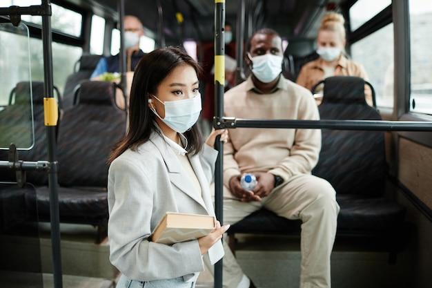 Vue latérale portrait d'une jeune femme asiatique portant un masque dans un bus lors d'un voyage en transports en commun en ville, espace pour copie