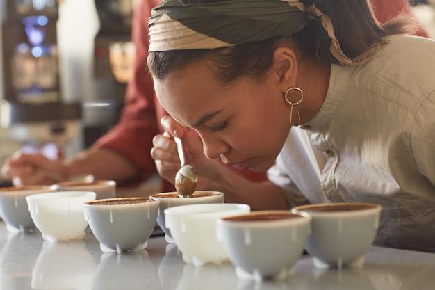 Vue latérale portrait d'une jeune femme métisse sentant le café lors de l'évaluation de la qualité et du test de dégustation au café, espace de copie