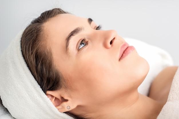 Vue latérale portrait de jeune femme pensive allongée sur une table d'esthéticienne en attendant la procédure cosmétique dans un salon de beauté