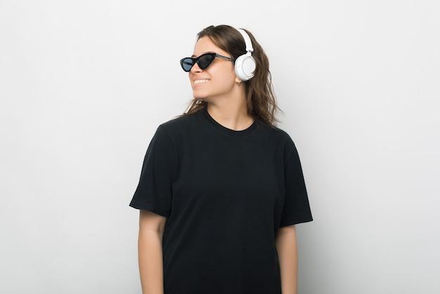 Vue latérale portrait d'une jeune femme portant des écouteurs.