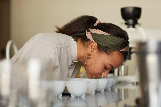 Vue latérale portrait d'une jeune femme sentant le café lors de l'évaluation de la qualité et du test de dégustation au café, espace de copie