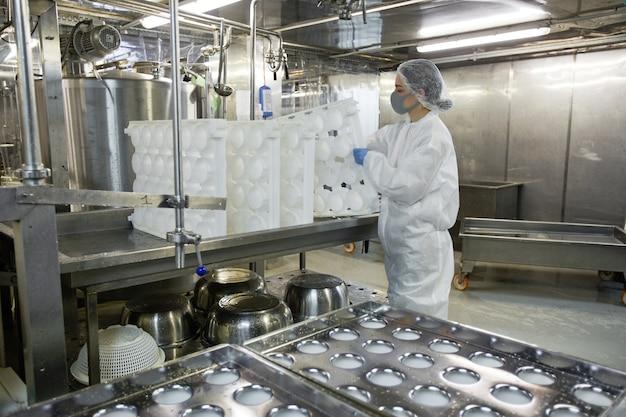 Vue latérale portrait d'une jeune femme travaillant dans une usine alimentaire et tenant des moules tout en portant des vêtements de protection, espace pour copie