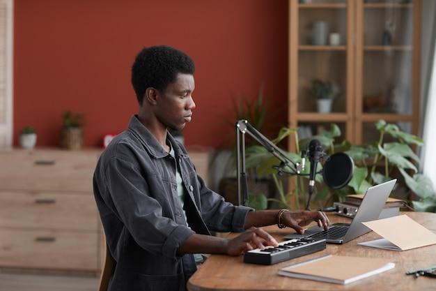 Vue latérale portrait de jeune homme afro-américain composer de la musique en studio d'enregistrement à domicile, espace copie