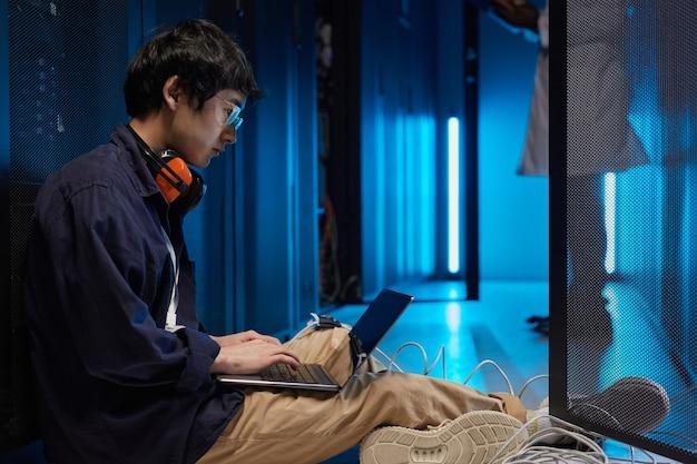 Vue latérale portrait d'un jeune homme asiatique assis sur le sol dans la salle des serveurs lors de la configuration du réseau de superordinateurs, espace de copie