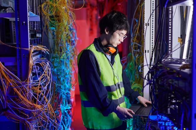 Vue latérale portrait d'un jeune technicien réseau utilisant un ordinateur portable dans la salle des serveurs lors de la configuration de la connexion internet, espace de copie