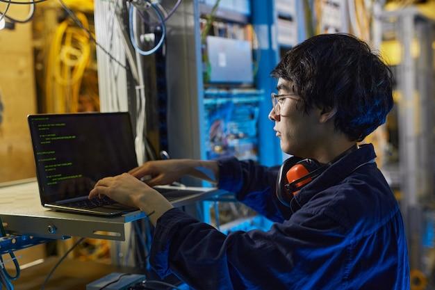 Vue latérale portrait d'un jeune technicien réseau utilisant un ordinateur portable lors de la configuration de la connexion internet dans la salle des serveurs, espace de copie