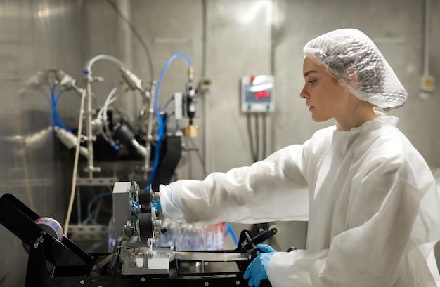 Vue latérale portrait d'une jeune travailleuse utilisant l'équipement tout en travaillant à l'usine, espace de copie
