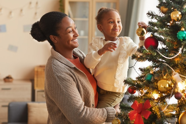 Vue latérale portrait de jolie fille afro-américaine décoration arbre de noël alors qu'il était assis dans les bras de la mère dans un intérieur confortable
