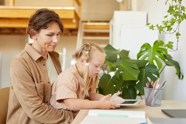 Vue latérale portrait de jolie fille avec le syndrome de down à l'aide de tablette numérique avec la mère tout en étudiant à la maison, copiez l'espace