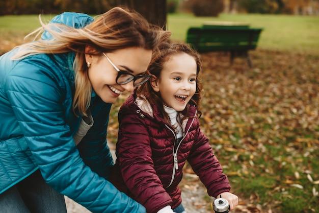 Vue latérale portrait d'une jolie petite fille apprenant à faire du vélo en riant avec sa mère dans le parc.