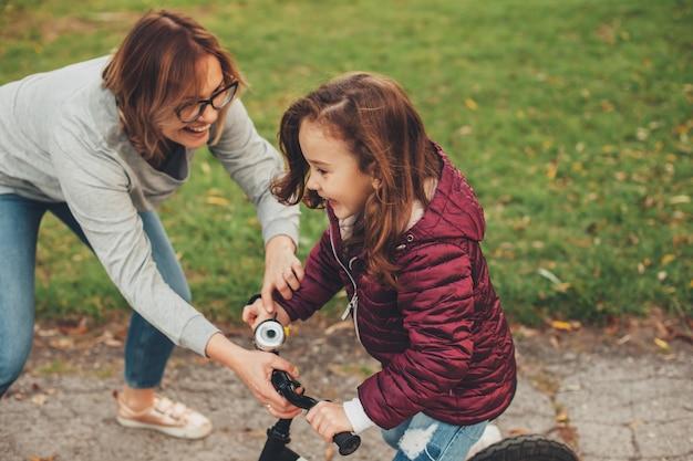 Vue latérale portrait d'une mignonne petite fille riant sur un vélo pendant que sa mère la surprend en train de rire en plein air dans le parc.