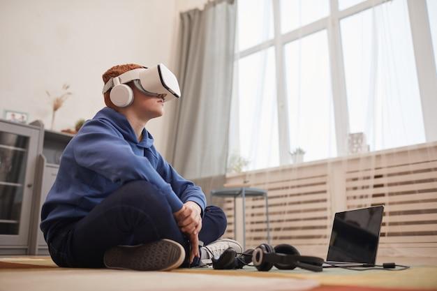 Vue latérale portrait o adolescent aux cheveux rouges portant un casque vr tout en jouant à des jeux vidéo assis sur le sol, espace pour copie