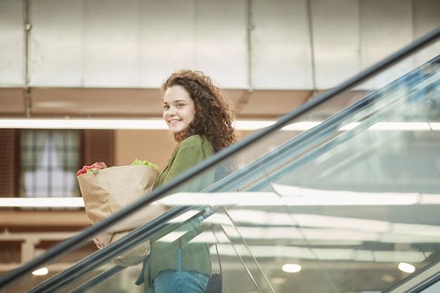 Vue latérale portrait of smiling young woman holding bag avec des produits d'épicerie en descendant l'escalator dans le centre commercial