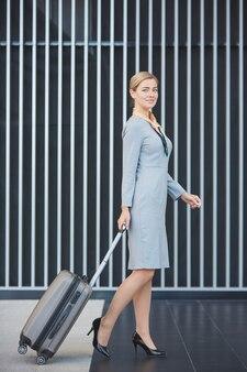 Vue latérale portrait de pleine longueur d'élégante femme blonde avec valise et souriant tout en marchant sur fond graphique à l'aéroport
