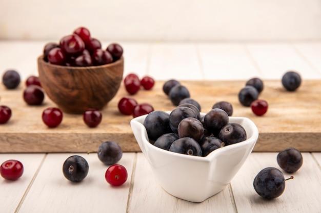 Vue latérale des prunelles violet foncé sur un bol blanc avec des cerises rouges sur un bol en bois sur une planche de cuisine en bois sur un fond en bois blanc