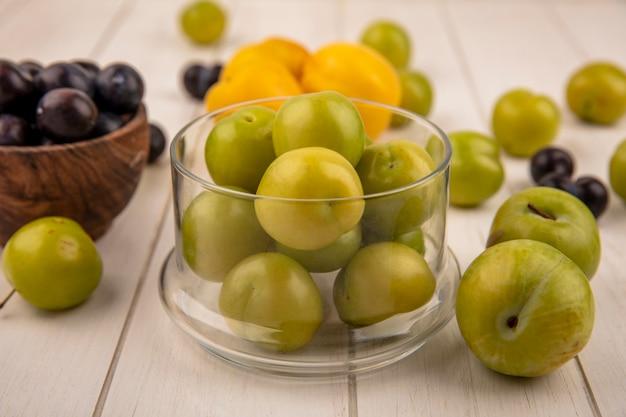 Vue latérale des prunes cerises vertes fraîches sur un bol en verre avec prunelles violet foncé sur un bol en bois avec des pêches isolé sur un fond en bois blanc