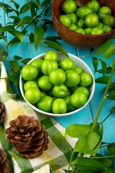 Vue latérale des prunes vertes aigres dans un bol et des cônes avec des feuilles de ruscus sur une table en bois bleue