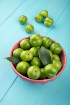 Vue latérale des prunes vertes aigres dans un bol sur une table en bois bleue