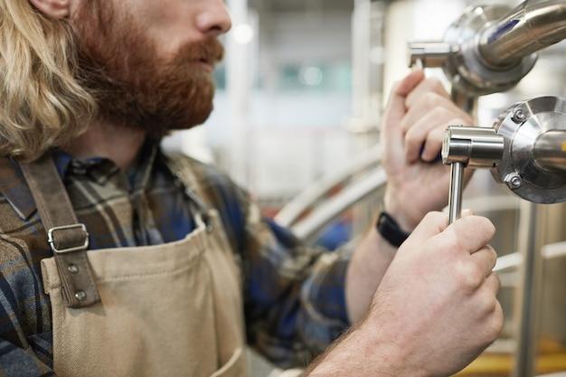 Vue latérale recadrée des machines d'exploitation du maître brasseur barbu à l'usine de fabrication de bière, espace de copie