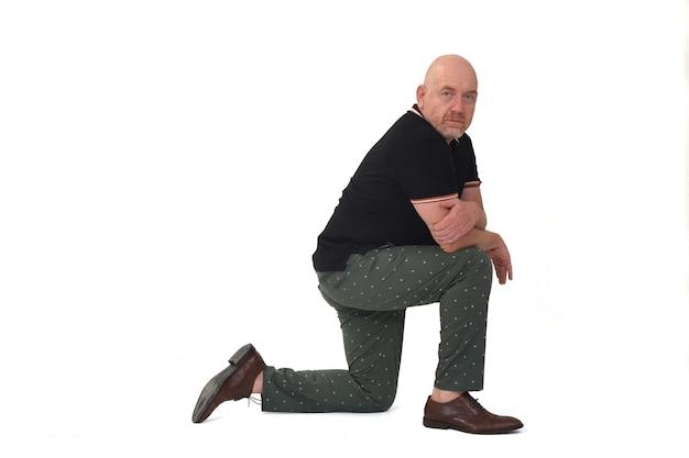 Vue latérale et regardant la caméra d'un homme sérieux s'appuyant sur un genou au sol sur fond blanc