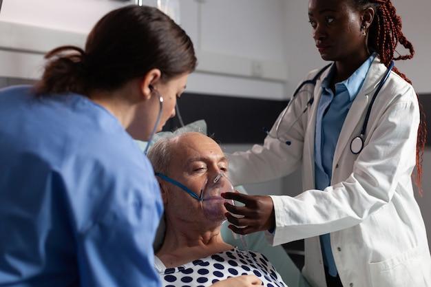 Vue latérale de la respiration du patient senior assistée par un tube respiratoire en soins intensifs hospitaliers