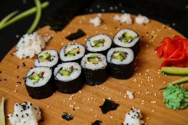 Vue latérale des rouleaux de kappa maki au gingembre wasabi et concombre sur un plateau