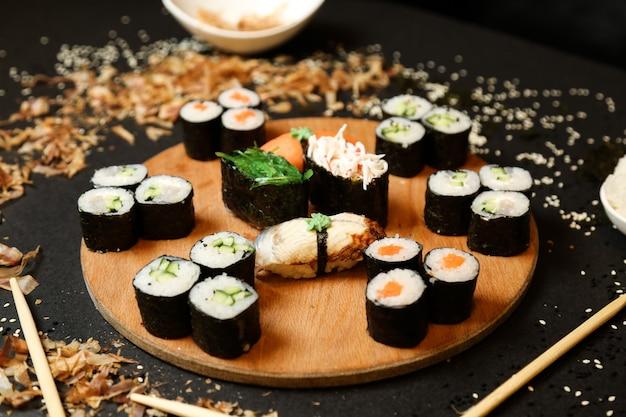 Vue latérale des rouleaux de kappa maki avec shake maki et sashimi sushi avec des baguettes sur un support